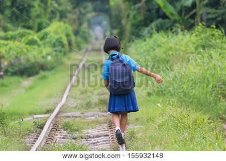 Thai schoolgirl in traditional costume walking and balancing on the railway of the Talat Phlu district in Bangkok.