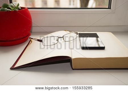 still life from a book phone and glasses