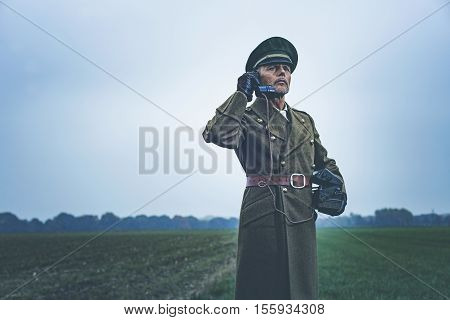 Vintage 1940S Military Officer Calling With Field Phone While Standing On Farmland.