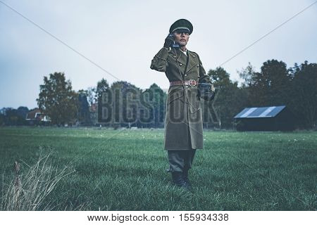 Retro 1940S Military Officer Calling With Field Phone While Standing On Farmland.