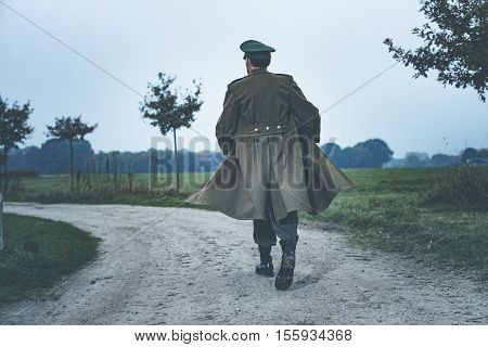 Rear View Of Vintage 1940S Military Officer Walking On Rural Road.