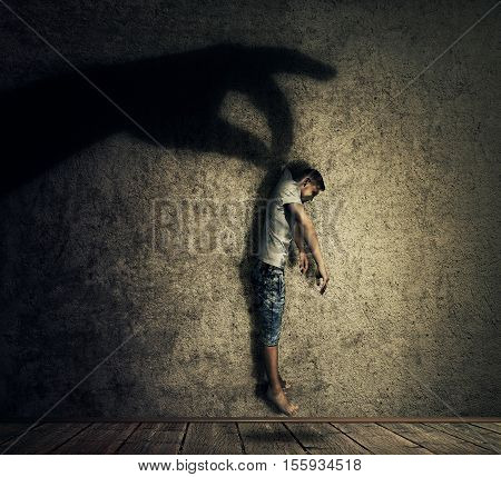 Human hand shadow holding a powerless man hanging. Conceptual image symbolizing manipulation business control as a marionette.