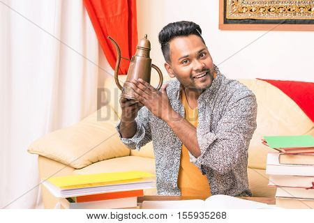 Young indian man rubbing old lamp is making wishes - Happy asian student at home holding copper cruet with hopeful facial expression - Funny concept of easy solutions in everyday teenage school life