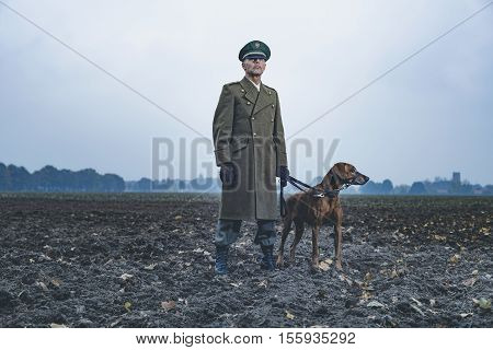 Patrolling Retro 1940S Military Officer Standing With Dog On Farmland.
