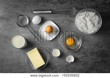 Ingredients for making cake on grey background, top view