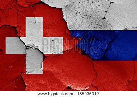 flags of Switzerland and Russia painted on cracked wall
