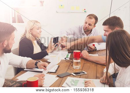 Business meeting. Young happy businessmen and women at modern office, team corporate discussion at workplace, show information on tablet. Brainstorming of partners for internet online shop startup