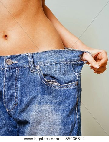Close-up Of Woman Belly In A Too Big Pants