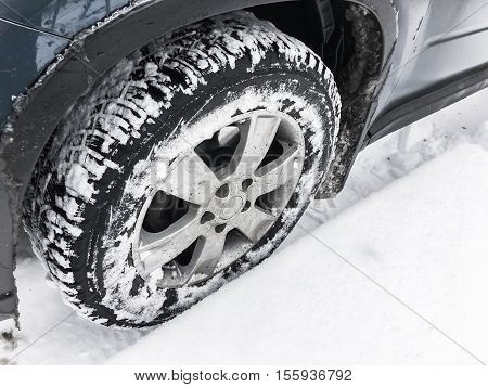 Wheel With Studded Tire Standing In Snow