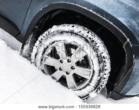Car Wheel With Studded Tire In Snowdrift