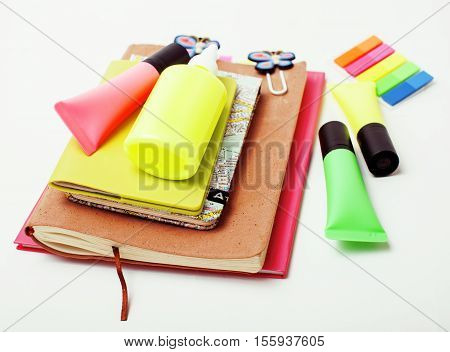 business, education and technology concept - close up of notebook, paper stickers, pencil different real stuff on white background