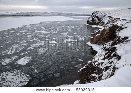 Winter landscape drifting ice floes surrounded by rocks