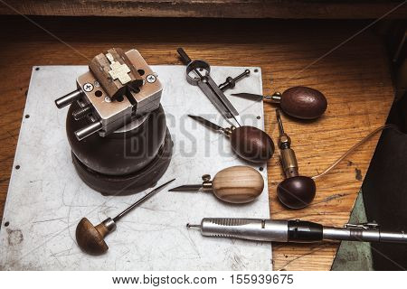 Cross in bullseye vise, gravers, compasses and drilling machine