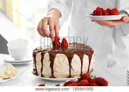 Female chef making caramel cake