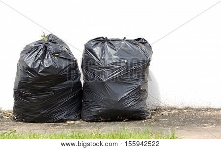 black garbage bags on the walkway and white wall background