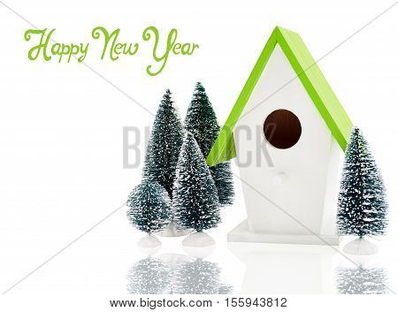 Christmas composition with bird house surrounded by fir trees isolated