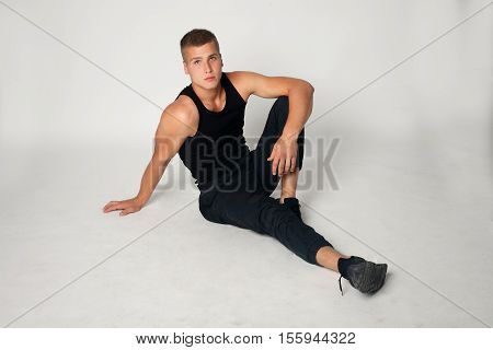 Expressive young stylish man in black t-shirt black pants black sneakers on a light grey background