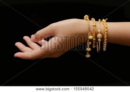 woman's hand with many different golden bracelets on black background
