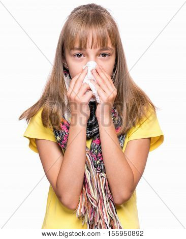 Healthcare and medicine concept - ill little girl with flu blowing nose.  Child wearing yellow t-shirt and scarf.