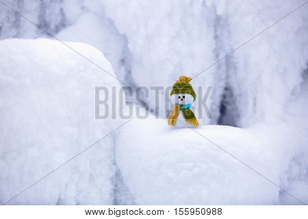 character snowman in hat and scarf is standing on fascinating fluffy snow near the hill and around there are frozen textured patterns.