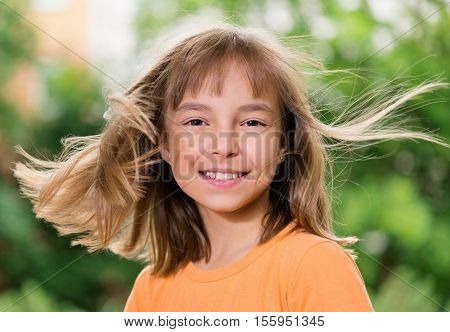 Portrait of a happy girl 10-11 year old, posing outdoors. Cute smiling child with flying hair looking at camera. Beautiful kid having fun in summer park.