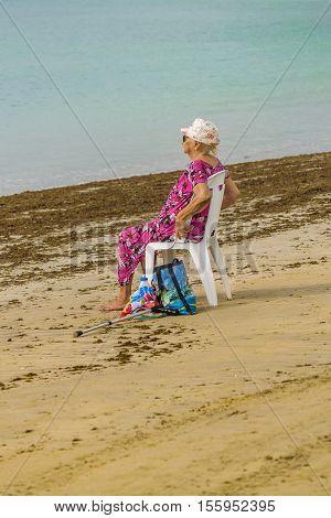 PORTO GALINHAS, BRAZIL, JANUARY - 2016 - Senior woman with colorful dress sitting on a chiar at beach in Porto Galinhas Pernambuco Brazil