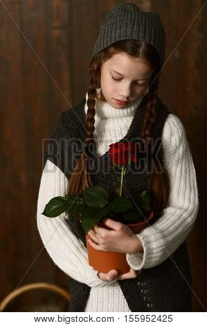 cute Girl in vintage clothes with knitted hat, pigtails, looking at flowers