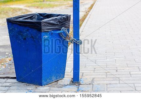 blue trash closed on the lock to a pole