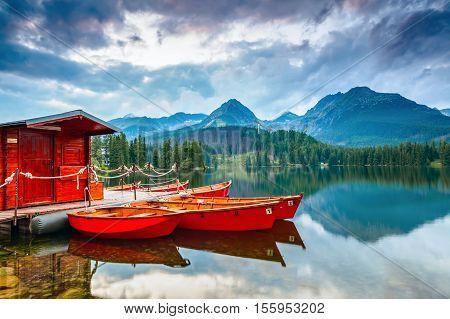 Dreamy boats stand near wooden bridge and a hut on a mountain lake on a spring day.Strbske Pleso lake Slovakia Tatra mountains.