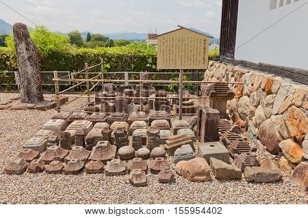 FUKUCHIYAMA JAPAN - JULY 29 2016: Gravestones displayed in the main bailey of Fukuchiyama castle. These stone objects were used in stone foundation of the castle main keep