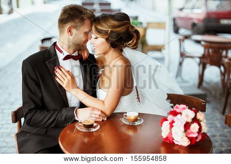Wedding photo shooting. Bride and bridegroom sitting in cafe, embracing and smiling. Bouquet and coffee on table near them. Outdoor, profile
