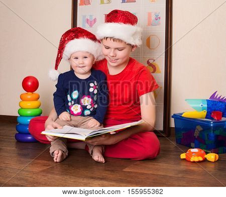 Happy children in Santa hats reading a Christmas book. Big brother reading to his little baby sister in the nursery.