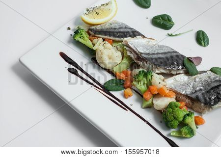 steam cooked mackerel fish with vegetables isolated; healthy sea food with lemon basil cauliflower and carrots;