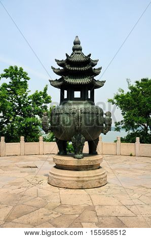 A weathered large buddhist prayer urn on three mount island overlooking Lake Tai or Taihu in Wuxi China in Jiangsu province
