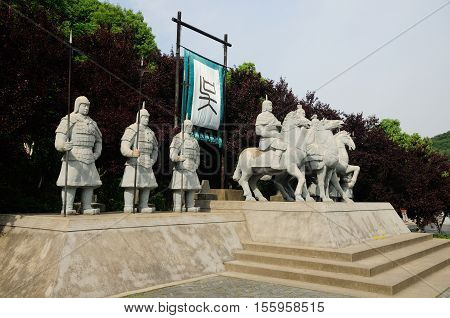 Old chinese foot and horse soldiers statues representing the Wu Kingdom before the Chinese family character at the Three Kingdoms scenic area in Wuxi China in Jiangsu province.