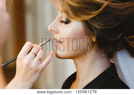 Pre-wedding preparation. Bride having her make-up done. Fiancee with closed eyes. Portrait, profile, closeup