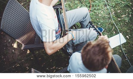 The guy playing on the black guitar in a musical group