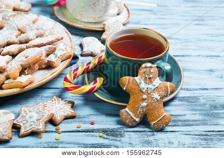 Christmas sweets baking gingerbread cookies on the plate. Decorated for Christmas gingerbread cookies christmas figurines bumps. Christmas cookies gingerbread on blue table tea drink. New Year food.