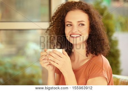 Attractive woman savouring coffee in cafe