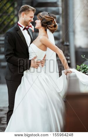 Wedding photo shooting. Bride and bridegroom looking at each other, smiling and embracing. Woman wearing white dress and veil and man wearing suit. Outdoor, full body, profile