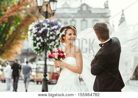 Wedding photo shooting. Bride and bridegroom walking in the city. Man holding bride's veil and girl smiling. Outdoor, waist up. Flowers, cobbled street, lantern
