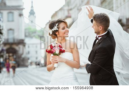 Wedding photo shooting. Bride and bridegroom walking in the city, looking at each other, holding bouquet. Groom holding veil of bride. Outdoor, cobbled street