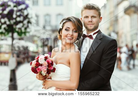 Wedding photo shooting. Bride and bridegroom in the city. Man embracing girl's waist from back. Holding bouquet. Bride turned a little bit aside. Outdoor, waist up