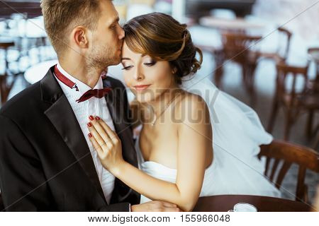 Wedding photo shooting. Bride and bridegroom sitting in cafe. Bridegroom kissing bride's forehead. Bride with closed eyes. Outdoor, waist up, closeup
