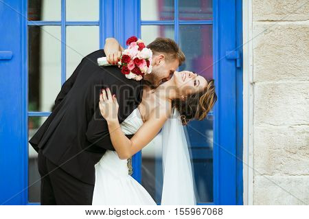 Wedding photo shooting. Bride and bridegroom near blue door. Embracing and leaning back, holding bouquet. Bridegroom kissing bride's neck. Outdoor