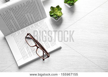 Glasses and open book on wooden table. Healthy eyes concept