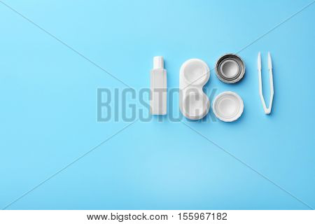 Container with contact lenses, tweezers and bottle of solution on blue background, close up view