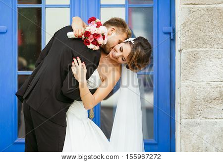 Wedding photo shooting. Bride and bridegroom near blue door. Embracing and leaning back, holding bouquet. Bridegroom kissing bride's neck and bride looking aside. Outdoor