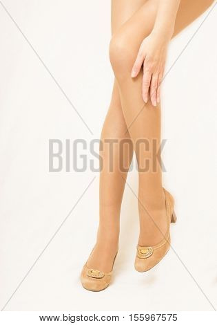 Women's legs in pantyhose and shoes. Neutral color