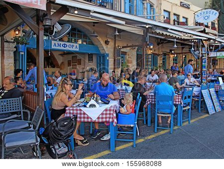 CRETE, GREECE - JULY 21, 2016: People sit in sidewalk street cafe in Chania waterfront on Crete island, Greece